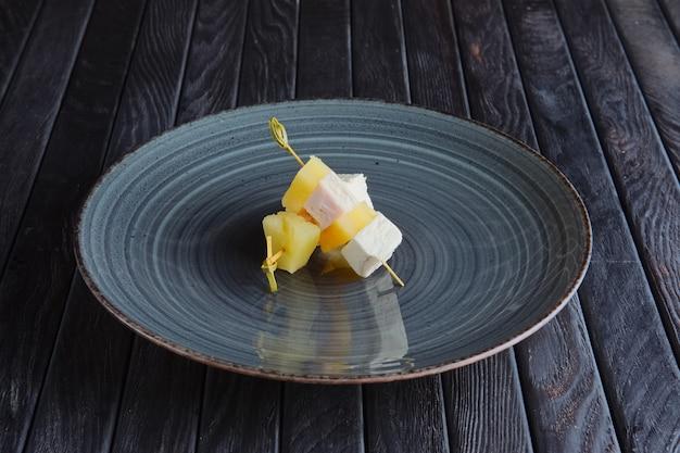 Закуска для приема. кусок куриного филе с моцареллой и ананасом на шпажке