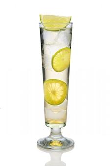 スパークリングワイン、ライム、レモンのスリングガラスを白で隔離されるカクテル