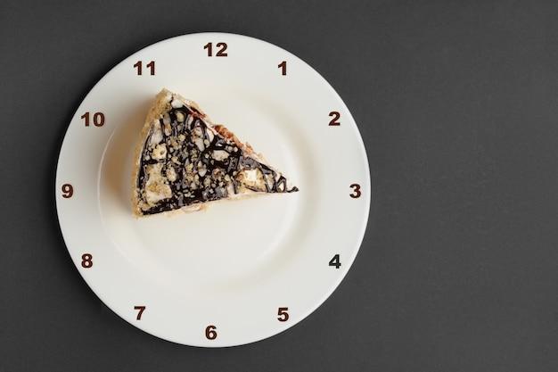 ナポレオンケーキ時計の文字盤が付いている皿の上のケーキ。上面図。