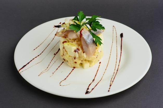 Вид сверху салата с кольцами сельди, яйца, яблока и лука