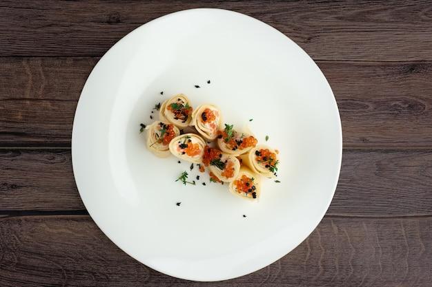 Вид сверху блины с лососем и икрой на большой белой тарелке