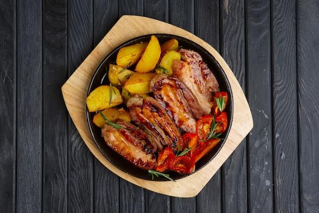 ポテトとトマトのリブの上の揚げ肉