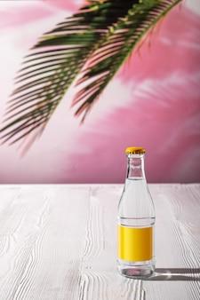朝の日差しの下で白い木製のテーブルの上のトニックウォーターの小瓶