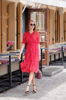 旧市街の通りを歩いて赤いドレスでかわいい女の子