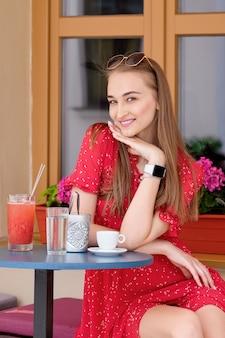 氷のような飲み物のグラスとカフェのテラスで休んで幸せな女の子