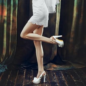 完璧なスリムな長い女性の足とウェディングドレス