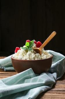 ラズベリーと木製のテーブルの上の粘土製品の木のスプーンで新鮮なカッテージチーズ