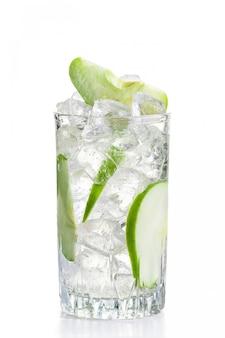 白で隔離される氷と冷たいアップルレモネードのガラス