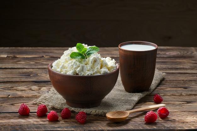 Творог и молоко в глиняной посуде на деревянный стол