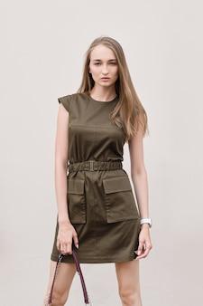 ミリタリースタイルのカーキ色のドレスでかわいい女の子