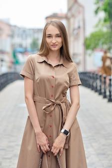 通りを歩いて長いオリーブのドレスで美しいモデル