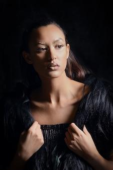 低キーの毛皮のベストと暗闇の中の革のズボンでかわいい女の子の肖像画を閉じる