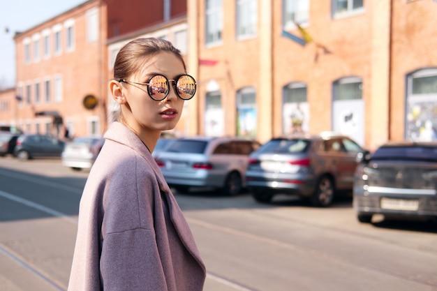 若い女の子が通りを横切っています。