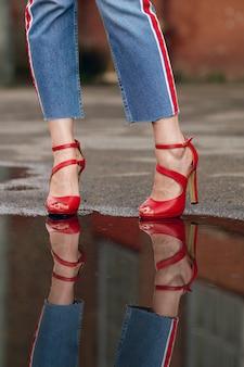 ジーンズの女性の足とアスファルトの上の水たまりに赤い靴の反射