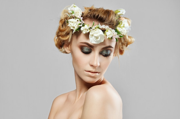彼女の髪に花を持つファッション美少女モデル。完璧なクリエイティブメイクアップとフローラルアートのヘアスタイル。