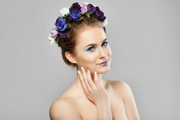 頬に触れる彼女の髪に花を持つファッション美少女モデル。完璧なクリエイティブメイクアップとフローラルアートのヘアスタイル。