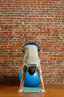 Атлетик делает упражнения для баланса на резиновый мяч