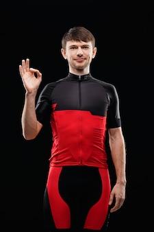 Спорт. велосипедист в тренировочной одежде на черном фоне показывает знак ок.