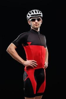 Спорт. велосипедист в тренировочной одежде на черном фоне.