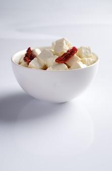 Чаша с кусочками сыра фета и вялеными томатами с маслом