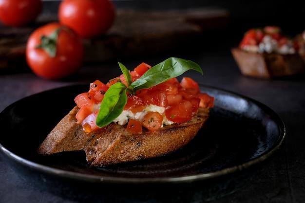 Брускетта с помидорами, базиликом и деревенским сыром на деревянной доске с помидорами таблицы. традиционная итальянская закуска или закуска