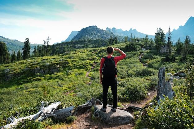 Туристический мужчина стоит на дороге и смотрит на вершину горы