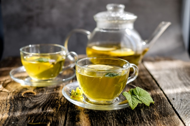 Травяной чай с лимоном и медом в стеклянной чашке и чайнике