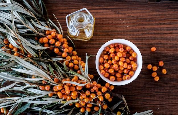 オレンジ色の海クロウメモドキの葉と果実、木製のテーブルにオイルのボトル