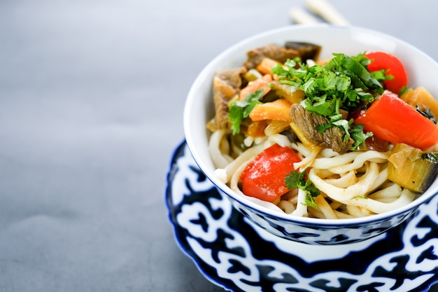 Национальное азиатское вкусное блюдо лагмана в тарелке на столе