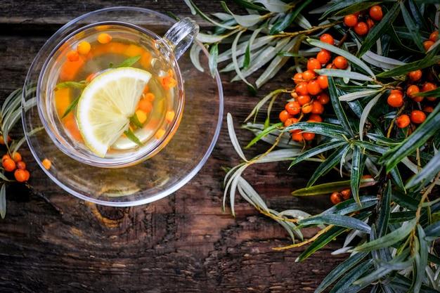 木製テーブルの上の新鮮な果実と熱い海クロウメモドキ茶のカップ