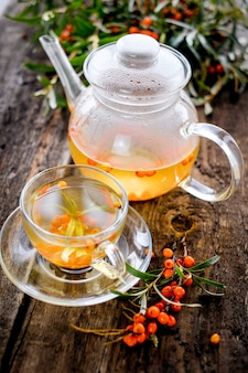 ティーポットと木製のテーブルに新鮮な果実と海クロウメモドキ茶のカップ
