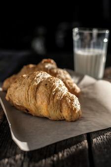 Вкусный завтрак со свежими круассанами и стакан молока на деревянный стол на солнечном свете