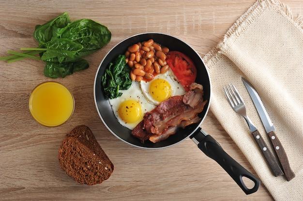 Яичница с беконом, шпинатом и фасолью на сковороде
