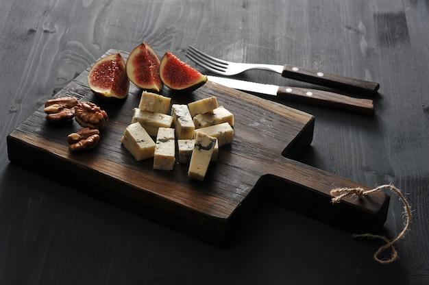 Голубой сыр, свежий инжир и грецкие орехи на деревянной доске и нож и вилка