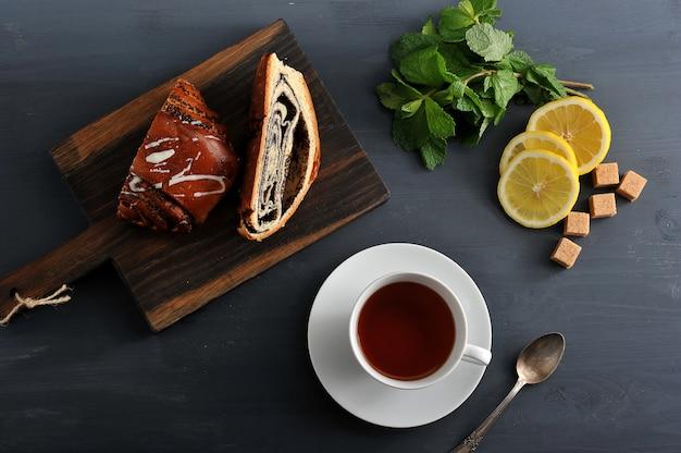 木製の表面にケシの実、紅茶、レモン、ミントを巻きます
