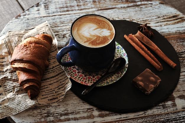 Утренний завтрак в кафе капучино в кружке, круассан, корица