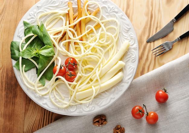 Сыр на тарелке с помидорами и базиликом с сулугуни, чечил, копченым сыром