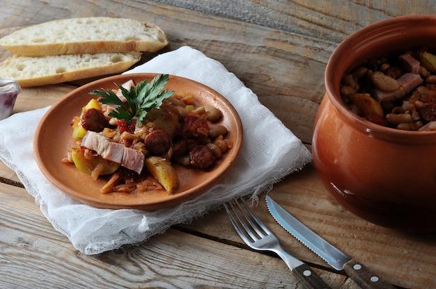 Блюдо, приготовленное в горшочке с картофелем, фасолью, копченое в глиняном горшочке