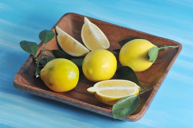 青の背景に皿の上の葉と新鮮な黄色いレモン