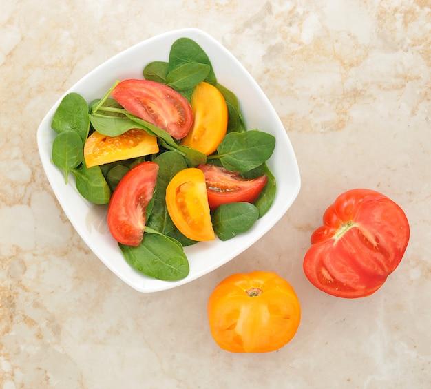 Салат с желтыми и красными помидорами и шпинатом