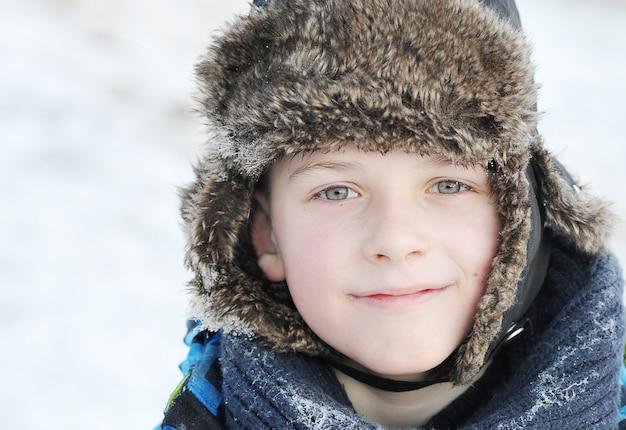 冬の冬の毛皮の帽子の小さな男の子