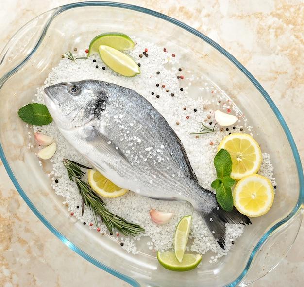 塩、ローズマリー、ニンニク、ライム、レモンのガラス皿にドラド魚