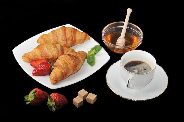 コーヒーと黒の表面に蜂蜜とクロワッサン