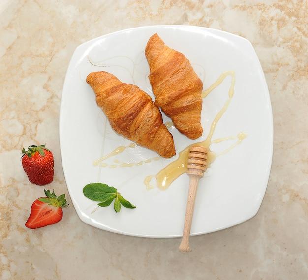 Два круассана на белой тарелке посыпать медом и клубникой