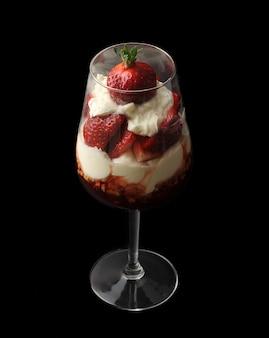 黒い表面にシャンパングラスにクリームとイチゴ