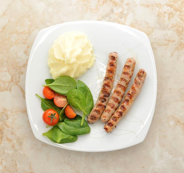 Колбаса гриль с картофельным пюре, шпинатом и помидорами