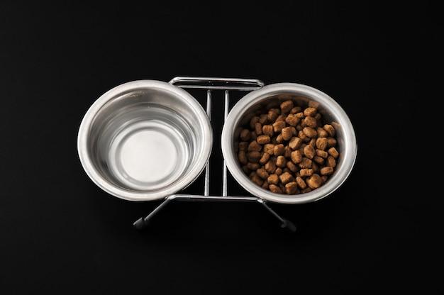 Корм для собак в металлической миске на черной поверхности