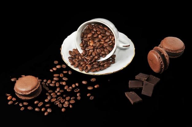 Чашка с кофейными зернами и шоколадными макаронами и кусочками шоколада