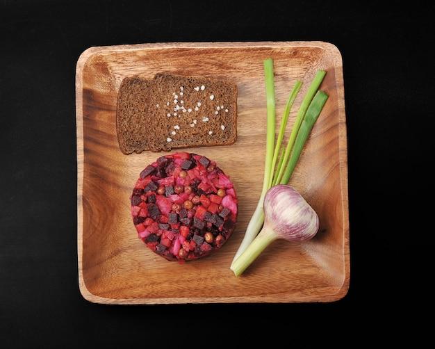 黒い表面にライ麦パン、塩、青ネギの木製プレートにビネグレット