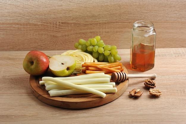 Различные виды сыра сулугуни, сыр и банка с медом